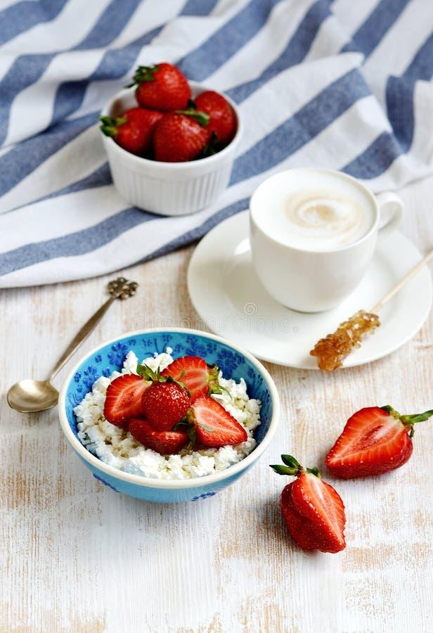 Hüttenkäse mit Erdbeeren, Schale mit Cappuccino-Getränk blüht hölzerne Hintergrund-Tabellen-Küche lizenzfreie stockfotografie