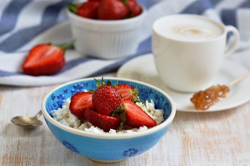 Hüttenkäse mit Erdbeeren, Schale mit Cappuccino-Getränk blüht hölzerne Hintergrund-Tabellen-Küche lizenzfreie stockbilder