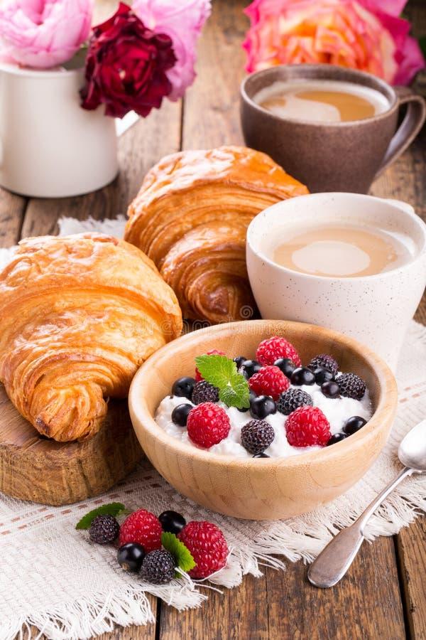 Hüttenkäse mit frischen Beeren, Tasse Kaffee und Hörnchen lizenzfreie stockbilder