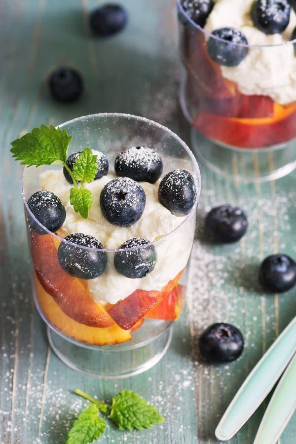 Hüttenkäsecreme mit Blaubeerbeeren und -pfirsich schneidet Nahaufnahme Köstlicher Nachtisch mit Beeren auf einem grünen hölzernen lizenzfreie stockfotos