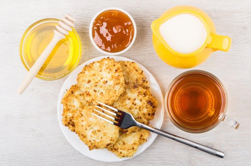 Hüttenkäsepfannkuchen, Honig, Krugmilch, Aprikosenmarmelade und Tee lizenzfreies stockfoto
