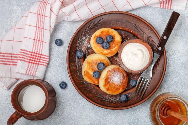 Hüttenkäsepfannkuchen, syrniki, Klumpenstückchen mit frischer Beerenblaubeere, Puderzucker, Milch, Honig und Sahne stockbilder