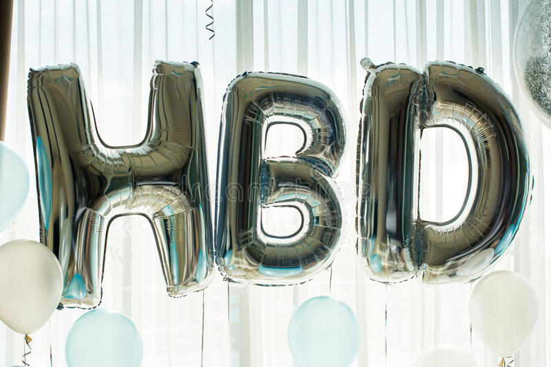 H B D Balloon in birthday party background. H B D English alphabet from silver balloons on a white curtain background. Happy Birthday balloons design for royalty free stock photography