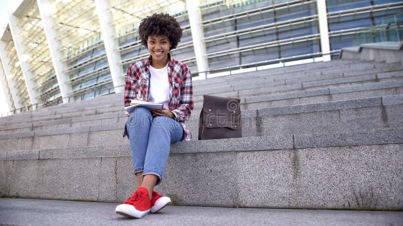 H?bsche afroe-amerikanisch Studentin, die drau?en Hausarbeit, l?chelnd in Kamera tut stockfoto
