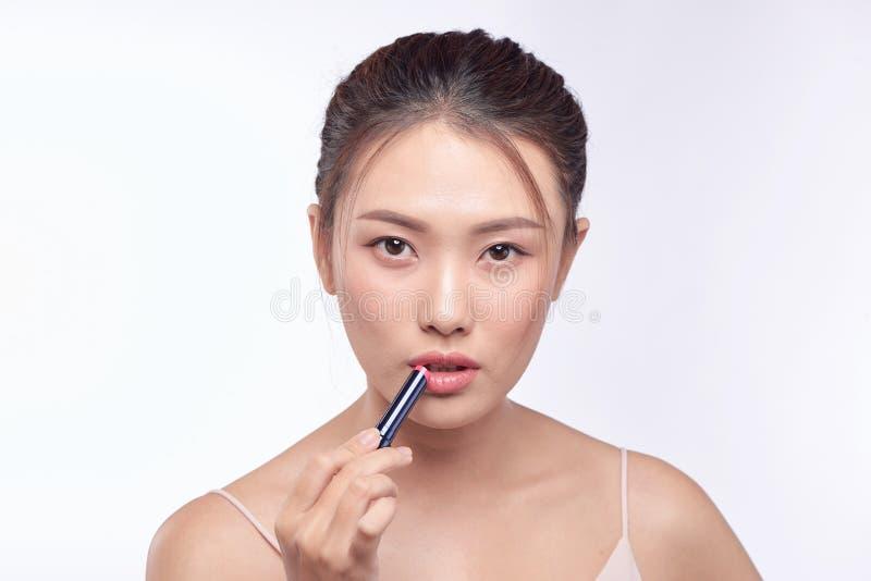 H?bsche asiatische Frau, die den Lippenstift, lokalisiert auf Wei? anwendet lizenzfreie stockfotos