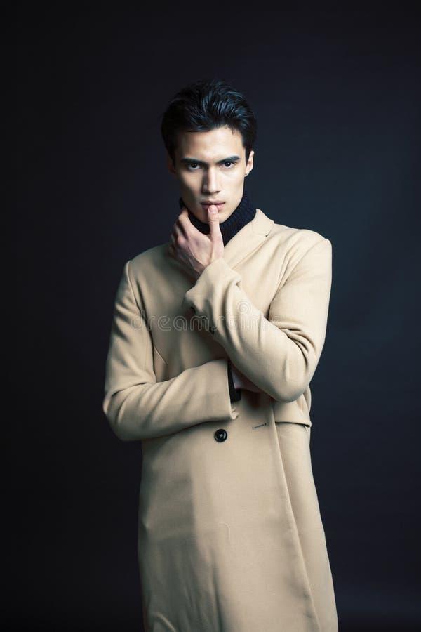 H?bsche asiatische Mode, die den Mann oben aufwirft im Studio auf schwarzem Hintergrund, Leute-Konzeptabschlu? des Lebensstils mo lizenzfreie stockfotografie