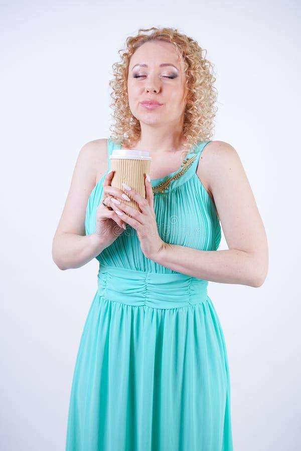 H?bsche blonde kaukasische Frau, die langes blaues Modesommerkleid auf wei?em Hintergrund tr?gt stockbild