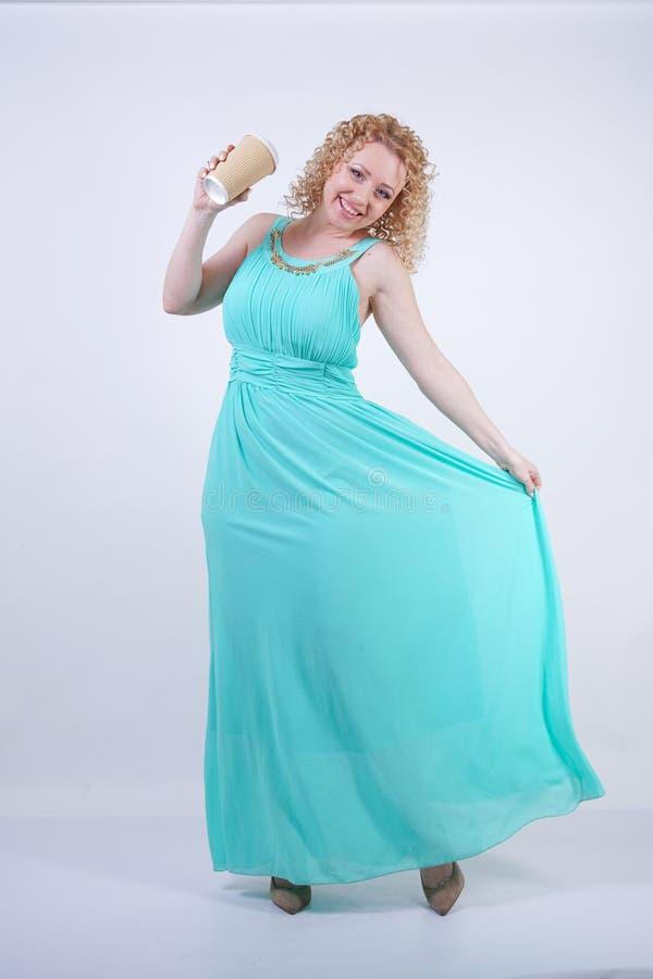 H?bsche blonde kaukasische Frau, die langes blaues Modesommerkleid auf wei?em Hintergrund tr?gt stockfoto