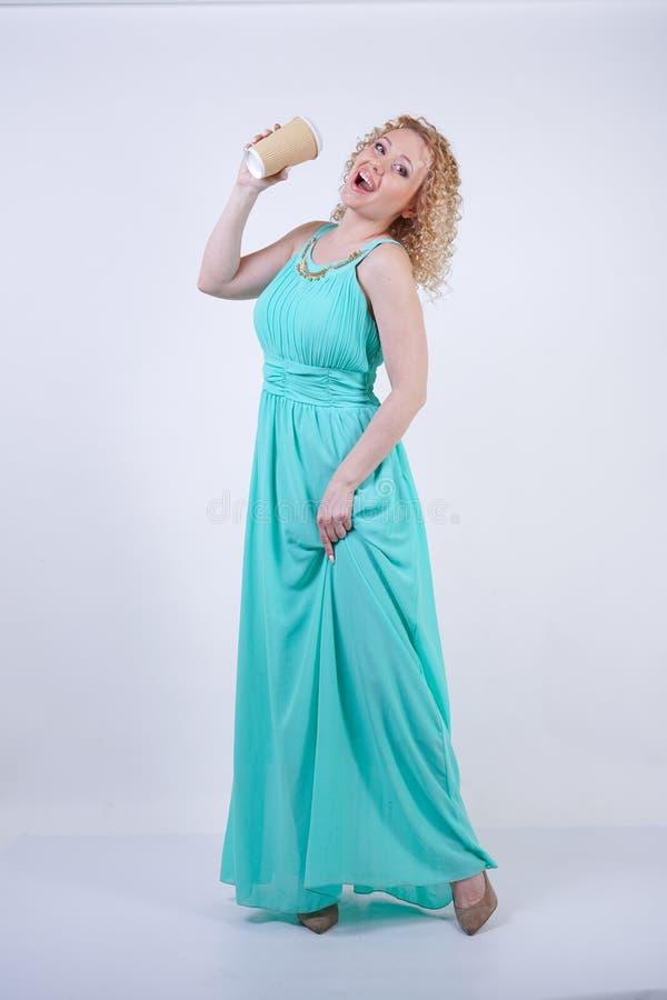 H?bsche blonde kaukasische Frau, die langes blaues Modesommerkleid auf wei?em Hintergrund tr?gt stockfotografie
