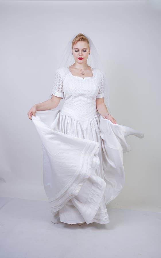 H?bsche curvy erwachsene Frau mit dem kurzen Haar, das langes Weinlesehochzeitskleid mit Sonnenartrock tr?gt junge kaukasische Br stockfotografie