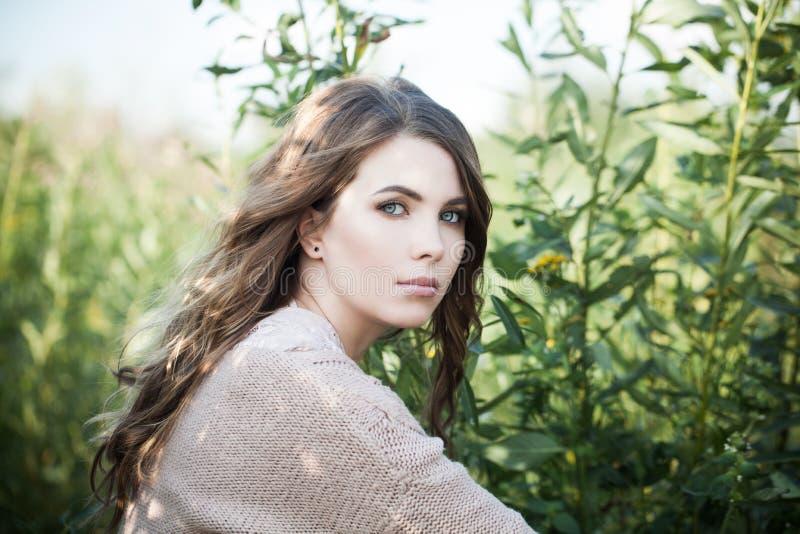 H?bsche Frau drau?en Schönes weibliches Modell in der Biobaumwollestrickjacke auf Hintergrund des grünen Grases stockfoto