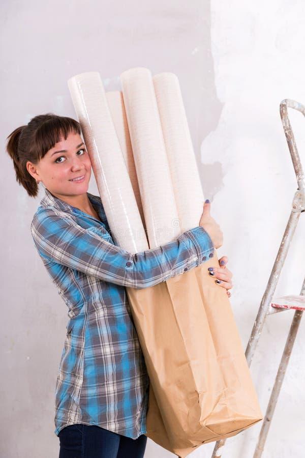 H?bsche Frau mit den Tapeten, die gehen, Haus zu reparieren lizenzfreie stockfotos