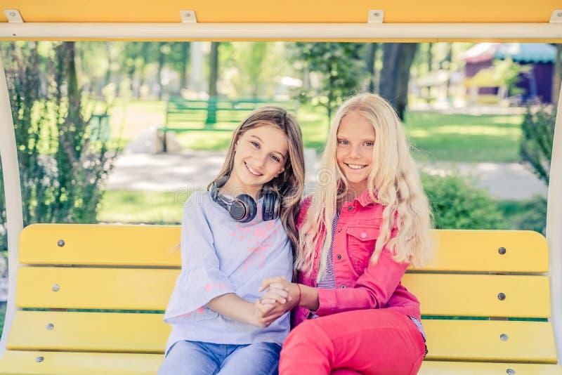 H?bsche l?chelnde Jugendlichen sitzen zusammen umarmen lizenzfreie stockfotos