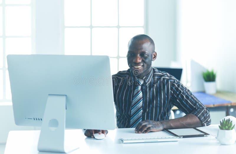 H?bscher afroer-amerikanisch Gesch?ftsmann in der klassischen Klage benutzt einen Laptop und l?chelt beim Arbeiten im B?ro stockfoto