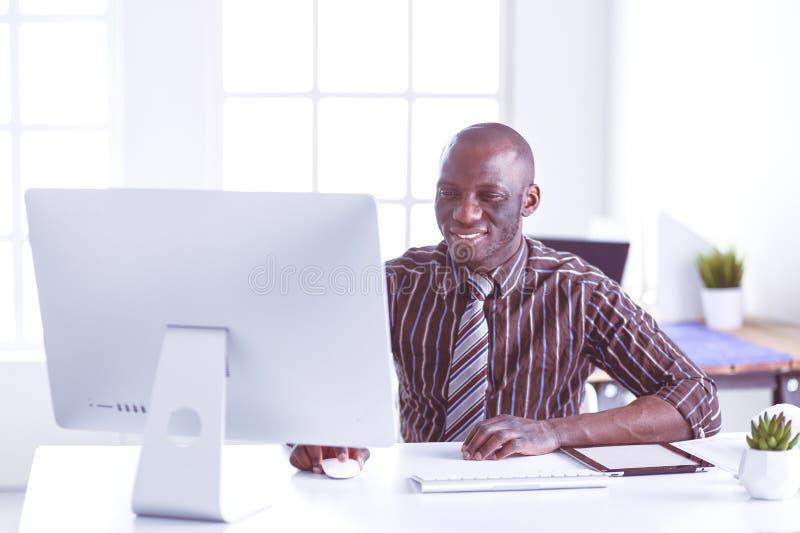 H?bscher afroer-amerikanisch Gesch?ftsmann in der klassischen Klage benutzt einen Laptop und l?chelt beim Arbeiten im B?ro stockfotografie