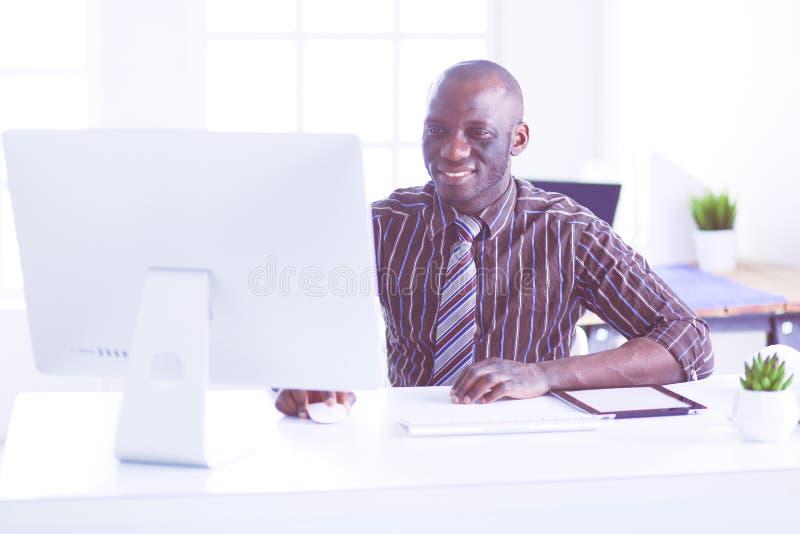 H?bscher afroer-amerikanisch Gesch?ftsmann in der klassischen Klage benutzt einen Laptop und l?chelt beim Arbeiten im B?ro lizenzfreies stockfoto
