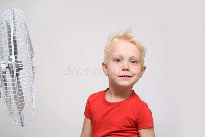 H?bscher blonder Junge im roten Hemd die k?hle Luft genie?end Seashells gestalten auf Sandhintergrund lizenzfreie stockfotos