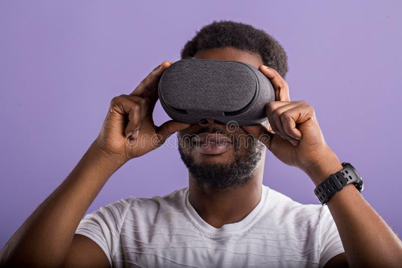 H?bscher junger afrikanischer Mann in der VR-Kopfh?rerstellung gegen purpurroten Hintergrund lizenzfreie stockfotografie