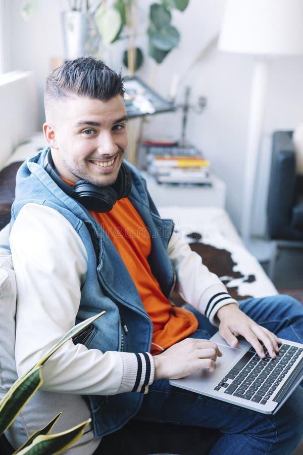 H?bscher junger Mann, der Laptop-Computer mit Kopfh?rer verwendet lizenzfreie stockfotos