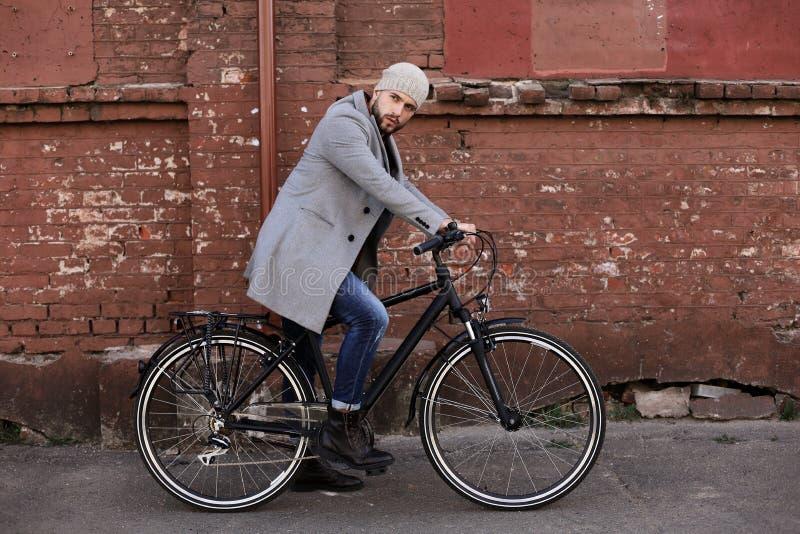 H?bscher junger Mann im grauen Mantel und im Hut, die eine Fahrradstra?e in der Stadt reitet stockbilder