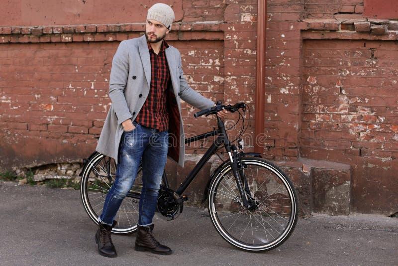 H?bscher junger Mann im grauen Mantel und im Hut, die sein Fahrrad hinunter eine Stra?e in der Stadt dr?ckt stockfoto