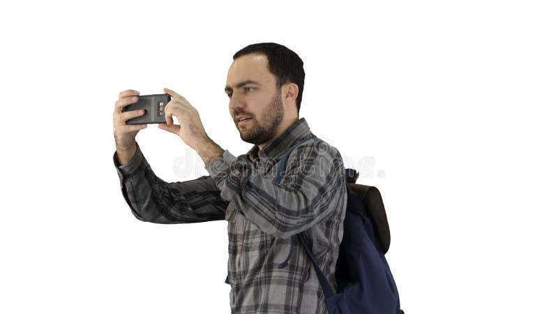 H?bscher tragender Rucksack des jungen Mannes und Machen eines Fotos von auf wei?em Hintergrund lizenzfreies stockfoto