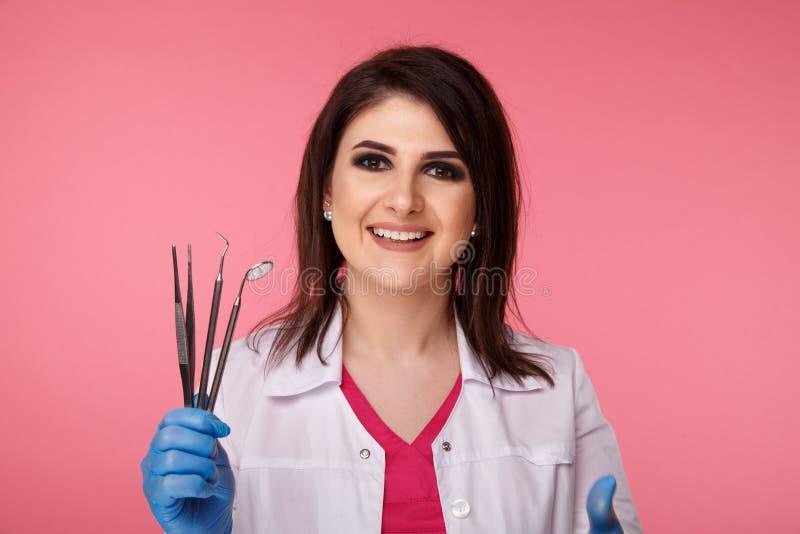 H?bscher Yong-Zahnarzt in den blauen Handschuhen mit dem medizinischen Werkzeug lokalisiert ?ber dem rosa Hintergrund lizenzfreie stockbilder