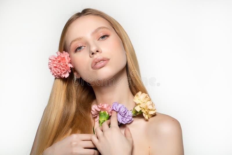 H?bsches junges blondes M?dchen mit der modischen Make-up und Klingelnblume gekr?uselt im Haar, Blumen auf der Schulter halten st stockfoto