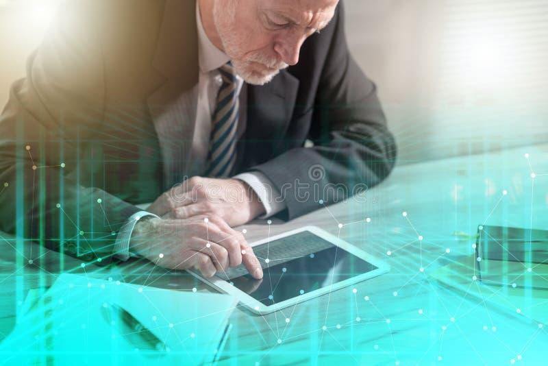 H?g aff?rsman som anv?nder en digital minnestavla; ?tskillig exponering royaltyfria bilder