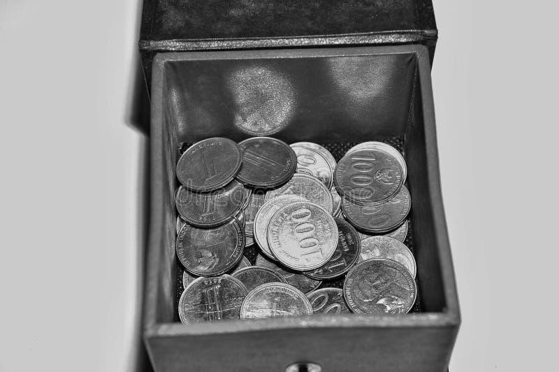H?g av det indonesiska myntet i asken som isoleras p? vit bakgrund royaltyfria foton