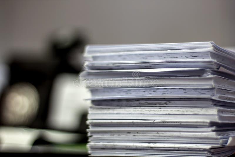 H?g av oavslutade dokument p? kontorsskrivbordet royaltyfri foto