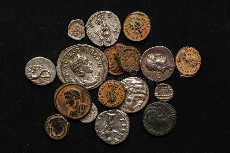 H?g av olika forntida mynt p? svart bakgrund arkivfoto