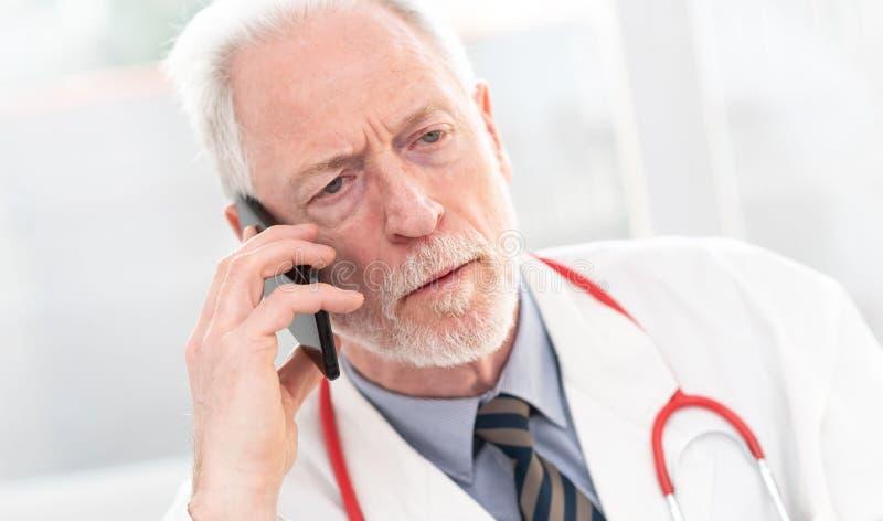 H?g doktor som talar p? mobiltelefonen royaltyfria foton