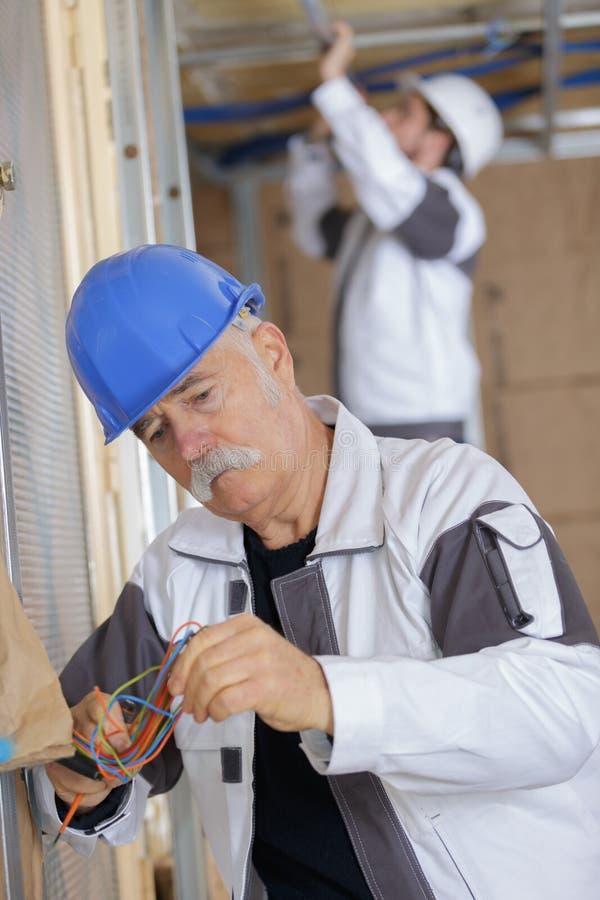 H?g elektriker som koncentrerar p? ledningsn?t royaltyfria bilder