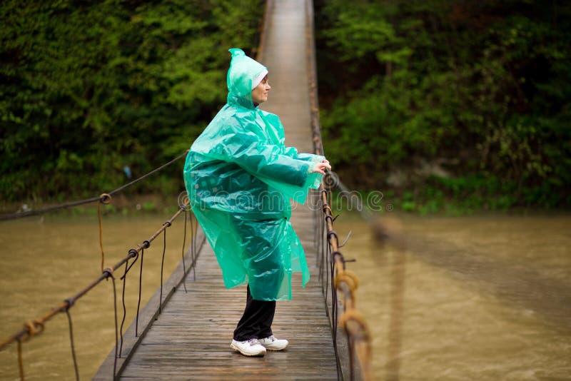 H?g kvinna 60 ?r gammal korsa flod vid den f?rs?g med g?ngj?rn bron i skog royaltyfri bild