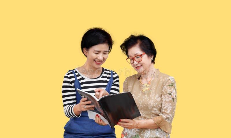 H?g kvinna som l?ser en tidskrift med hennes dotter royaltyfri bild