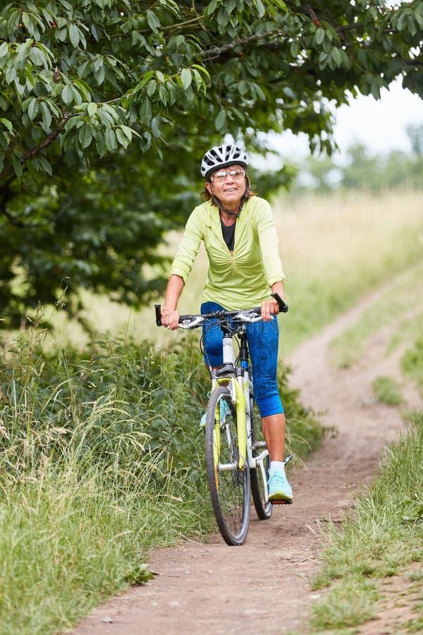 H?g kvinna som reser med mountainbiket royaltyfri fotografi