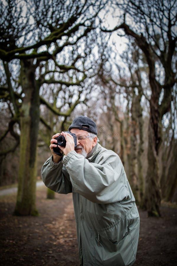 H?g man som ?gnar tid till hans favorit- hobby - fotografi royaltyfria bilder