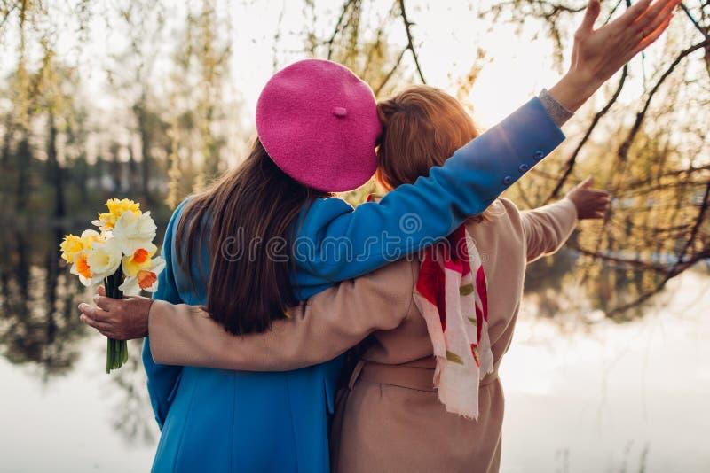 H?g moder med blommor och hennes vuxna dotter som kramar vid v?rfloden Fostra dagbegreppet f?r ` s Familjev?rderingar arkivfoton