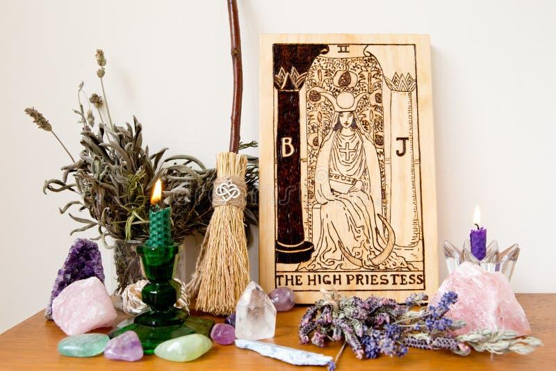 H?g Priestess fr?n taroken Major Arcana med kvasten, stearinljuset och kristaller arkivfoto