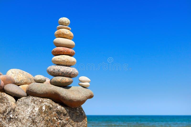 H?g pyramid av stenar av olika f?rger p? bakgrunden av havet och bl? himmel royaltyfri bild