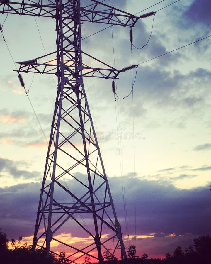 H?g-sp?nning kraftledningar p? solnedg?ngen Elektricitetsf?rdelningsstation arkivbild