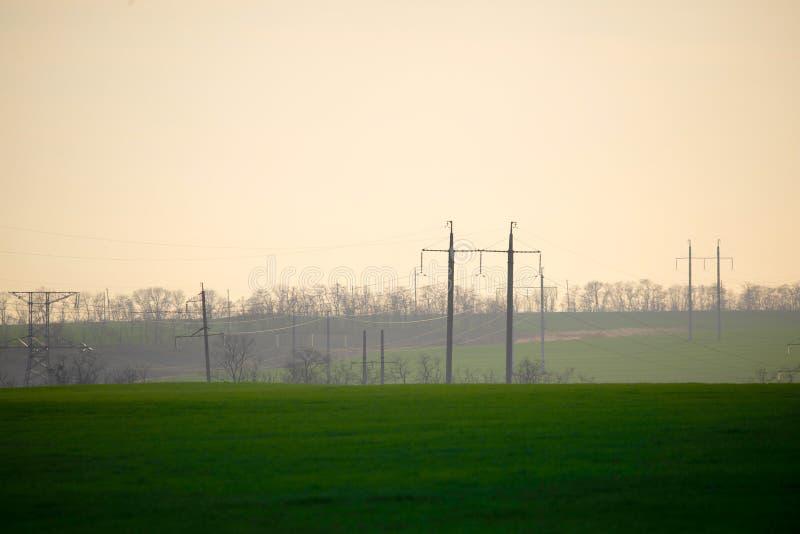 H?ga sp?nningslinjer och maktpoler och gr?nt jordbruks- landskap under soluppg?ng Anslutning av jordbruk och bransch i ett royaltyfri bild