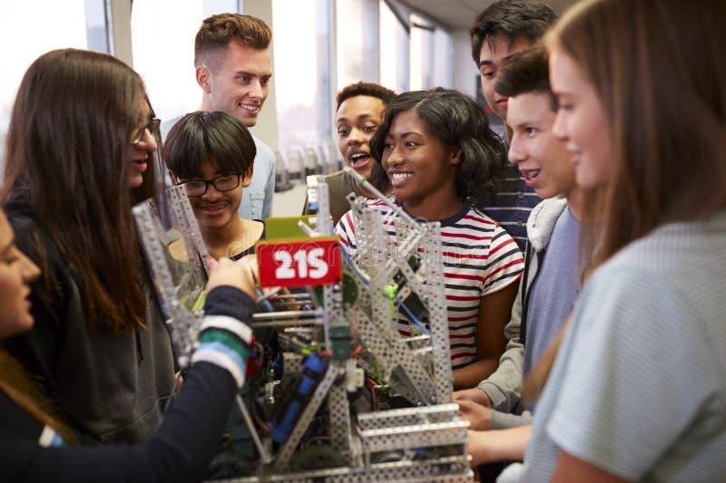 H?gskolestudenter med l?rareHolding Machine In vetenskap eller robotteknikgrupp arkivbilder