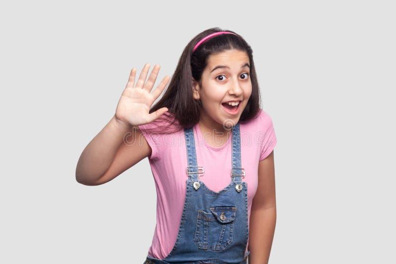 H?gt Stående av den förvånade härliga brunettunga flickan i tillfällig rosa t-skjorta och blåa overaller som står med den häpna f royaltyfri foto