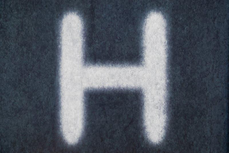 H isolerad kritabokstav i svart tavlabakgrund arkivbilder