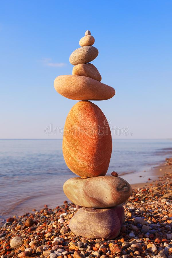 H?jdpunkten vaggar zenpyramiden av vita och rosa kiselstenar p? en bakgrund av bl? himmel och havet arkivbild