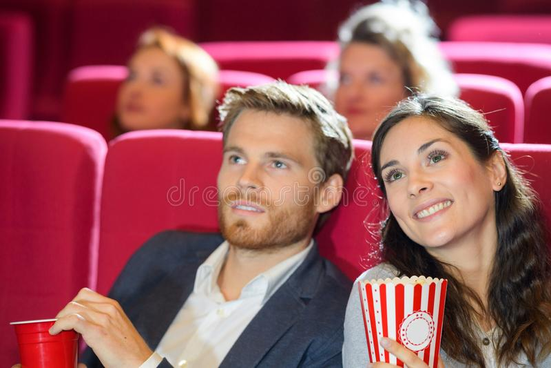H?llande ?gonen p? film f?r lyckliga par i teater royaltyfri fotografi