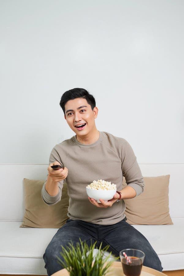 H?llande ?gonen p? TV f?r lycklig man och ?tapopcorn som placeras p? en soffa som isoleras p? vit bakgrund royaltyfria bilder