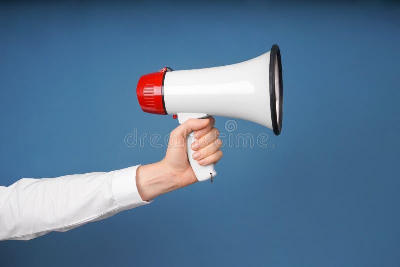 H?llande megafon f?r kvinna p? f?rgbakgrund arkivfoto